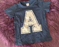 Mörkblå t-shirt med ett stort tryckt A från Lindex stl 92