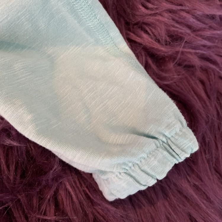 Turkosmelerad jumpsuit med volangärm och fickor från PoP stl 56