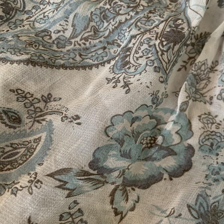 Ljust blågrå skir blus med ett paisleymönster i olika blå nyanser från Rabalder stl 100
