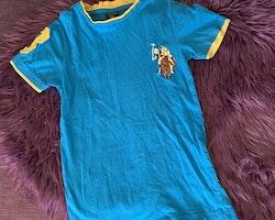 Blå t-shirt med gula detaljer samt gula, bruna, vita och svarta applikationer från U.S Polo Assn. stl 116