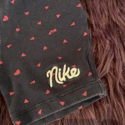 Mörkblå cykelbyxor/shorts med rosa figurer och broderat märke från Nike stl 80