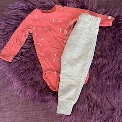 Orangeröd body med vita och svarta fåglar och gråa collegebyxor med detaljer i samma röda färg från Ebbe stl 62