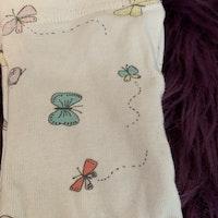 Ljusrosa omlottbody med flerfärgat text- och fjärilstryck samt matchande byxor i vitt med fjärilar från Lindex stl 50