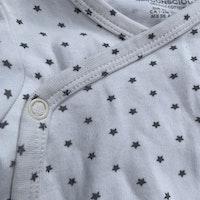 Litet vitt och grått fyrdelat set med omlottbody, byxor, haklapp och strumpor från HM Conscious stl 56