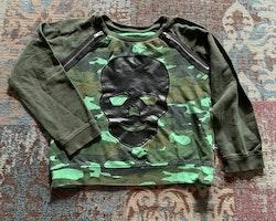 Grön kamouflagemönstrad tröja med dragkedjor och svart läder döskalle från The Brand stl 104/110