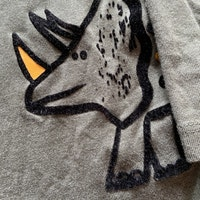 Grågrön tröja meddinosaurietryck i vitt, orange och svart sammet från Primark stl 98