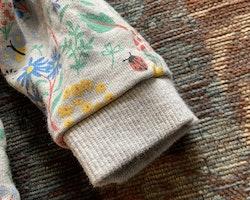 Grå collegetröja med färgglatt mönster av blommor och insekter från HM stl 68