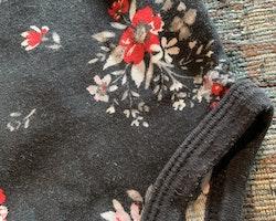 En ljusrosa och en mörkgrå body med små blommigt mönster från Carter's stl 6 mån