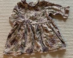Set med ljuslila klänning med lila blommönster och spets samt en matchande lila stickad kofta från Newbie stl 62