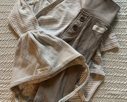 Tre delat set med vit omlottbody med beigea ränder och matchande mössa samt ett par helt beigea byxor från Newbie stl 62 + 40/42