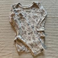Body och byxset i vitt med rosa, blått och grått blommönster från Newbie stl 62