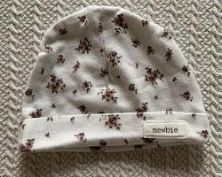 Vit mössa med ljuslila små blommor från Newbie stl 0-3 mån
