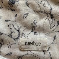 Vit haklapp med mörkblått mönster av ekorrar och ugglor från Newbie stl OS