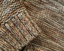 Stickad tröja melerad i olika bruna, grå och vita nyanser från NeXT stl 86