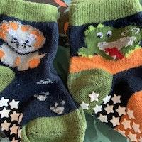 3 delat paket med halkstrumpor i grönt, orange, svart och vitt med en krokodil, ett lejon och ränder stl 19-21