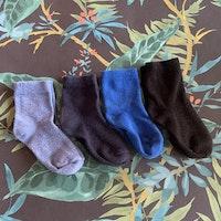4 delat paket strumpor i svart och tre olika blå nyanser stl 19-21
