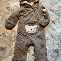 Brunmelerad lättfodrad tygoverall med stickade detaljer, ficka på magen med teddybjörnhuvud och huva med öron från Newbie stl 68