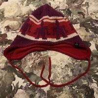 Lila, röd och vit stickad vintermössa med mönster från PoP stl 48/50