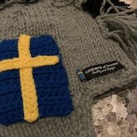 Grå och svart stickad mössa med en mohawk av garn och virkade svenska flaggor från Lundmyr of Sweden stl 0-6 mån
