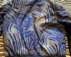 Grå bomberjacka med svart och blått växtmönster samt mörkblå muddar från Lager 157 stl 90