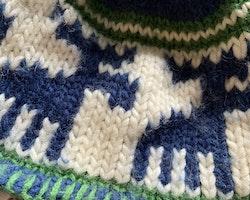 Vit, grön och blå stickad ullmössa med fleecefoder, älgmönster och tofs från PoP stl 48/50
