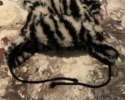 Svart och vit zebrarandig fluffig öronprydd mössa med snören från Åhléns stl 50