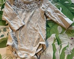 Beigemelerad body med blommönster i dova toner och dimmrosa mjukisbyxor från Lindex stl 74