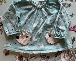 Ljusblå klänning/tunika med svartvitt mönster av gräs och kaniner samt två kaninformade fickor från PoP stl 68