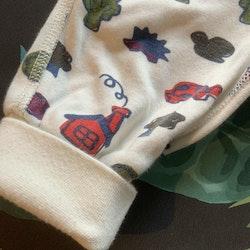 Vita byxor med mönster av massor med olika motiv som en igelkott, luftballong mm i dova mörka färger från PoP stl 62