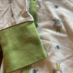Vit omlottbody med gröna kantband och ett grönt, ljusbrunt och blått ko- resp. vattenkannemönster från PoP stl 68