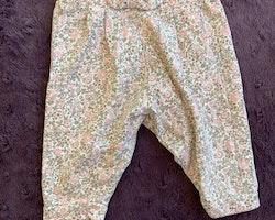 3 delat paket med byxor varav ett par mörkblå med volanger, ett par småblommiga i ljusrosa och grönt samt ett par leggings i samma färger från Newbie stl 56