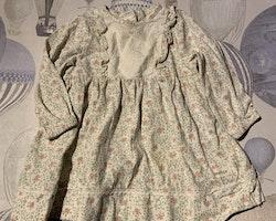 Vit klänning med blommigt mönster i grönt och rosa samt vit hålbroderad spets från Newbie stl 62