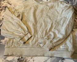 Beigemelerad tröja med puffärmar dekorerade med hålbroderi i vitt från Newbie stl 110/116
