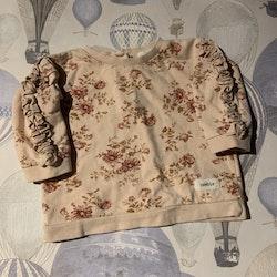 Ljusrosa collegetröja med volanger och blommönster i  olika rosa och bruna nyanser samt ett par bruna byxor med dekorerade fickor från Newbie stl 62