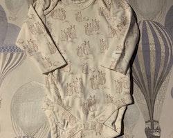 Två vita bodies med beige resp. vinrött mönster med ekorrar och igelkottar från Newbie stl 62