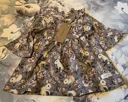 3 delat paket med en lila klänning med djur- och blommönster, lila volangleggings och en vit haklapp från Newbie stl 68 & OS