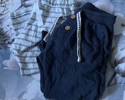 Två par mjukisbyxor, ett par mörkblå och ett par vita med blå ränder från Newbie stl 86