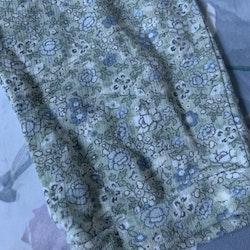Ljusgröna byxor med blommönster i vitt samt olika blå och gröna nyanser från Newbie stl 86