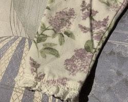 Vita leggings med vit virkad spets och lila och grönt syrenmönster från Newbie stl 68