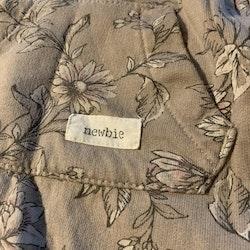 Ljusbrun jumpsuit med blommönster i mörkgrått, vitt och lila från Newbie stl 56