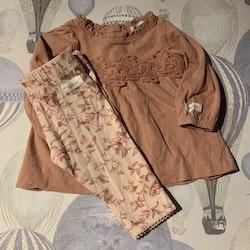 Rosa tunika med ton i ton spets och ett par ljusrosa leggings med rosa och mörkrosa blommönster från Newbie stl 62