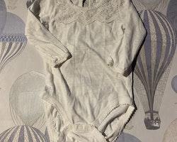 Vit body med vacker spets och ett par vita leggings med virkad spets från Newbie stl 62