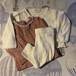 3 delat paket med en rosa body med blommor i olika rosa nyanser och grönt, en vit hålstickad omlottkofta och ett par vita leggings med broderade blommor från Newbie stl 68