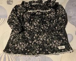 Mörkgrå klänning med volanger, virkad vit spets och ett blommönster i vitt, grönt och lila från Newbie stl 62