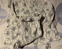 Set med vit tunika/klänning med mörkblått blommönster och matchande byxor med volangkant från Newbie stl 68
