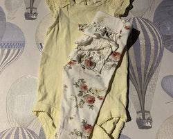 Ljusgul body med hålbroderad volangärm och ett par vita volangleggings med rosmönster i olika gula, gröna och rosa nyanser från Newbie stl 62