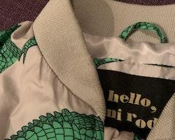 Beigegrå jacka med gröna krokodiler från Mini Rodini stl 92/98