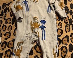 Ljusgrå jumpsuit med apor, bandspelare och palmer från Mini Rodini stl 56/62