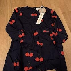 Marinblå långärmad vävd klänning med röda körsbär från Mini Rodini stl 104/110
