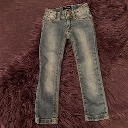 Jeans och en gråmelerad t-shirt med svart tiger- och texttryck från Mini Rodini stl 92/98